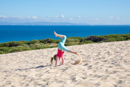 four years old girl doing handstand or somersault on sand dune of Valdevaqueros (Tarifa, Cadiz, Andalusia, Spain), with ocean and Africa on the horizon
