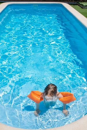 overhead view of four years old blonde child with orange floater sleeves in arms, armbands, in blue beautiful water, standing on stairs of swimming pool