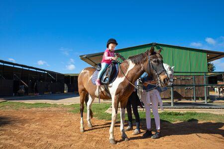 kleines Mädchen, das außerhalb des Stalls in einer Reitschule lernt, ein Pferd zu reiten?