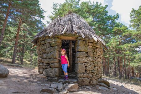 mountaineer five years old girl standing and looking at door frame of ancient hut in forest of Canencia mountain (Madrid, Spain, Europe)