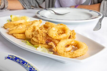 close up white tray with rings of squid, breaded and fried, with lemon and lettuce, typical food of Andalusia (Spain, Europe) on white tablecloth of restaurant ready to eat