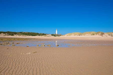 beautiful landscape: lighthouse of Trafalgar Cape reflected in water on sand of Beach Varadero or Marisucia, in Canos Meca village (Barbate, Cadiz, Andalusia, Spain)