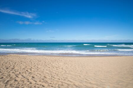 front view of seashore of Palmar Beach with sand, turquoise ocean water and horizon in Vejer village (Cadiz, Andalusia, Spain)