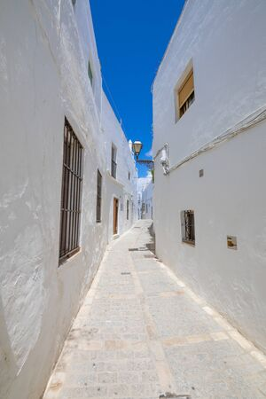 vertical shot: narrow pedestrian street in typical white houses Andalusian village named Vejer de la Frontera (Cadiz, Andalusia, Spain, Europe)