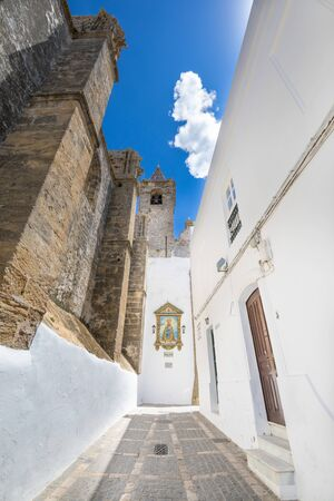 vertical shot of alley in a side of Church of the Divine Savior, from XVI century, public monument in Andalusian village named Vejer de la Frontera in Cadiz (Andalusia, Spain, Europe)