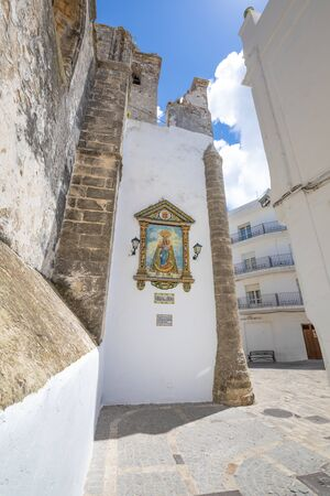 corner in alley with ancient painted sculpture on wall, public monument of Virgin Olive in typical Andalusian village named Vejer de la Frontera in Cadiz (Andalusia, Spain, Europe)