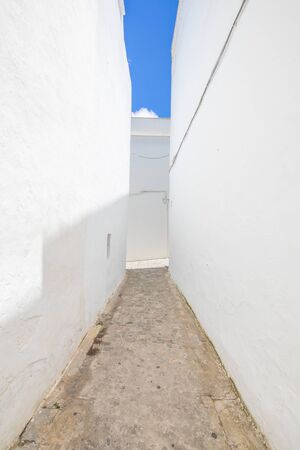 vertical shot of pedestrian alley narrowing in famous Andalusian old town, with typical arabic white houses, named Vejer de la Frontera (Cadiz, Andalusia, Spain, Europe)