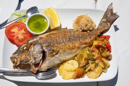 tray with a grilled fish known as Donkey or Borriquete (Plectorhinchus mediterraneus) in Spain, with potatoes and vegetables, rice, lemon and tomato Stockfoto