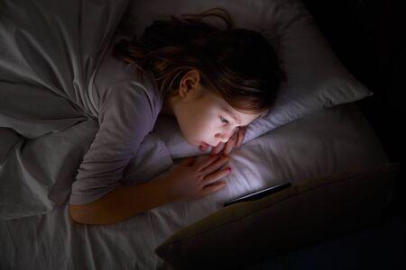 Fillette de six ans allongée sur un lit blanc la nuit en regardant un téléphone portable