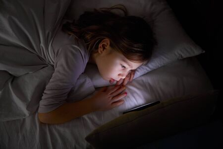 six years old girl lying on white bed at night watching mobile phone