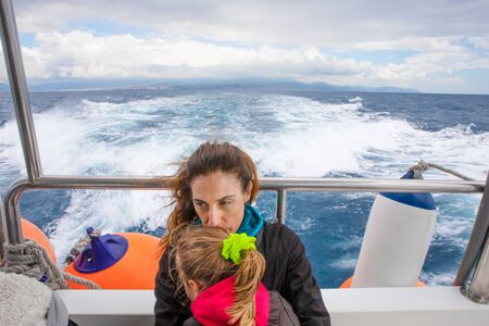 woman hugging her daughter, four years old blonde girl with pigtail, sitting on the stern of motor boat sailing from Tarifa (Cadiz, Andalusia, Spain) in Strait of Gibraltar