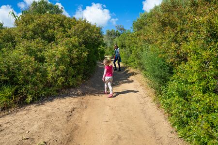 four years age blonde child with pink shirt walking, next to her mother woman turned and looking on a path in the forest of Cadiz, Spain