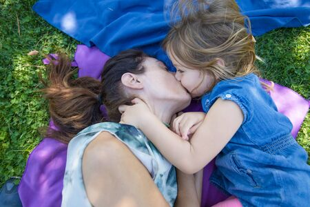 four years old blonde child kissing in mouth to woman mother, lying on blue and purple towels in the green grass of park