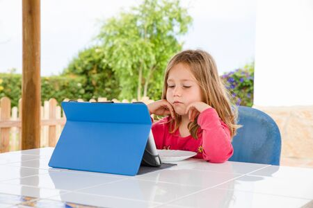 Four years old blonde girl with red shirt sitting, resting head in hands, watching digital tablet on the table