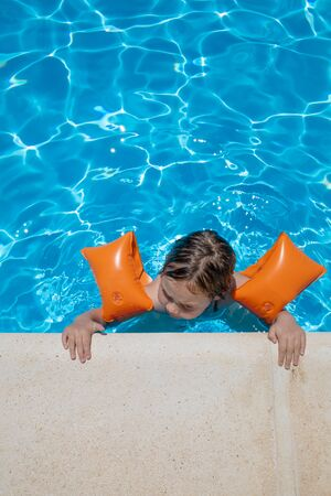 aerial shot: four years old blonde child with orange floater sleeves in arms, armbands, clinging or holding on to the curb of the swimming pool, with blue transparent water