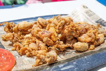 close view of baby little squids breaded and fried, typical food of Andalusia known as chopitos, in Spain, Europe