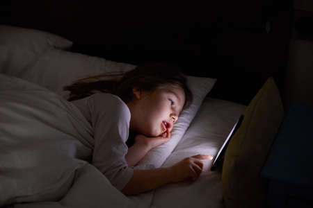 six years old girl lying on white bed at night touching digital screen mobile phone