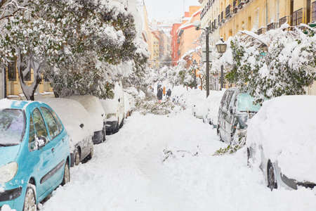 Street of Madrid city after a big snowfall, in Spain. Snow covering road, cars and trees. People walking. January 2021.