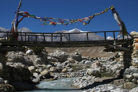 festooned: A wooden footbridge festooned with prayer-flags crosses a mountain stream near Garphu in Upper Mustang in Nepal with the Himalayas in the background. At an attitude of around 3,897 meters above sea level, Garphu is north of Lo Manthang, capital of the one