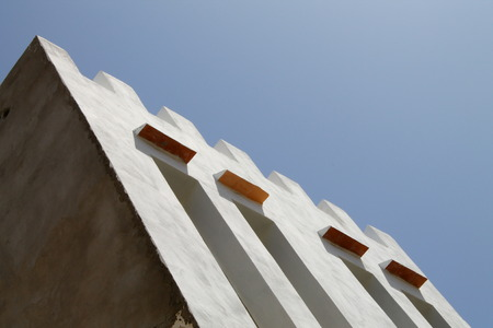 ramparts: The ramparts atop this building in Essaouira, Morocco contrast with the perfect blue of the sky along a pleasing diagonal. Stock Photo