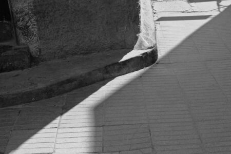 an ally: This black and white image brings out the light and shadow cast by sunlight around the corner of an ally in Essaouira, Morocco. Stock Photo