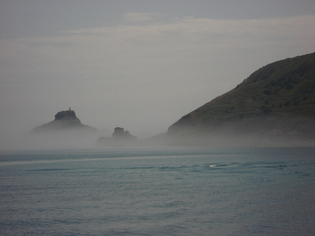 guernsey: The edge of the island of Jethou in light mist as seen from the Herm passenger ferry. Jethou is close to Guernsey in the Channel Islands.