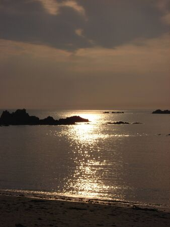 guernsey: Sunlight glistens from a calm sea during a warm summer afternoon at Cobo beach in Guernsey, Channel Islands.