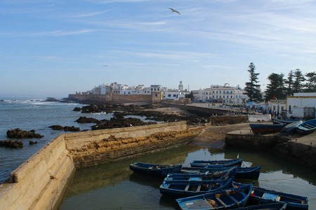 fishingboats: A view of Essaouria across the harbour to the coastal walls with wooden fishing-boats in the foreground. Stock Photo