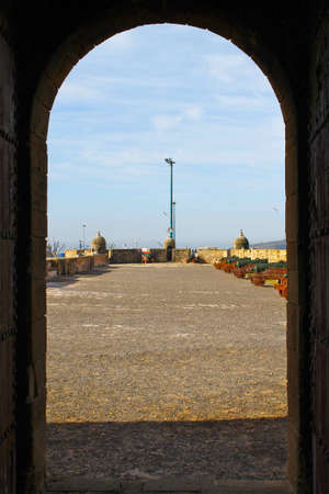 archways: A view of the ramparts above Essaouira harbour taken through the archway of its protective tower.