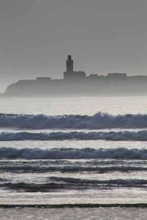 mystique: A view of the Isle de Mogador from the beach at Essaouira, Morocco. The high surf creates a series of horizontals that compare with the far coastline, while haze lends a sense of mystique to the Isle de Mogador.