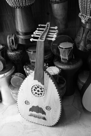 companions: A black and white study of a Moroccan Oud or lute, reveals the textures of the woods and materials of the instrument and its companions.