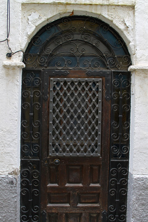 ironwork: An arched doorway reveals a wooden door with a grille and decorative ironwork in Granada, Spain.