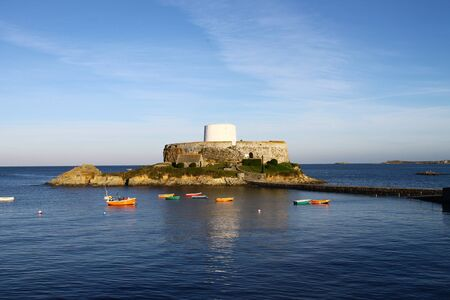 fishingboats: Fort Grey in a calm sea on a fine autumn morning. Situated on Guernseys west coast at Rocquaine, at high tide Fort Grey becomes an islet that can be reached by causeway. The bay forms a protective harbour for local fishing boats that can be seen moored i
