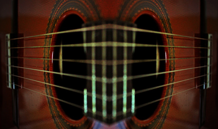 fretboard: This close up reflection of a classical guitar almost gives the abstract impression of a face or mask with large eyes and a fret-board nose.
