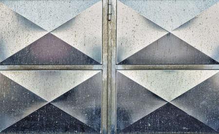 Section of unpainted, panelled steel garage door showing some weathering