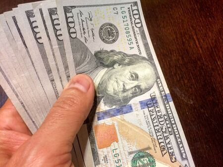 Stack of cash held in left hand over brown wooden table with Ben Franklin