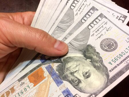 American Cash with Ben Franklin held in hand showing Federal Reserve System Seal