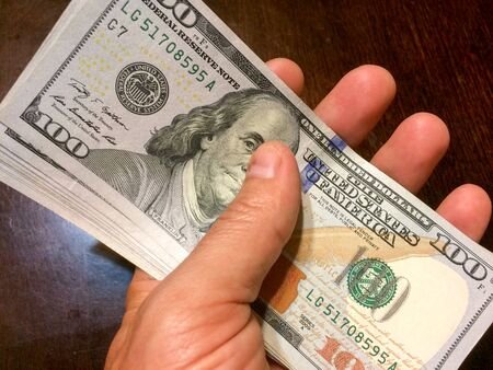 Stack of money held in hand over brown wood table