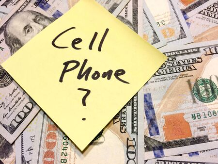 American cash money and yellow sticky note with text Cell Phone with question mark in black color aerial view