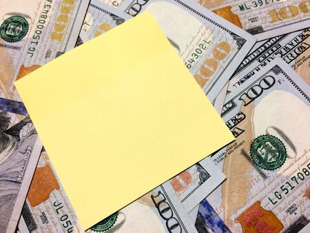 American cash money and blank yellow sticky note in aerial view Imagens