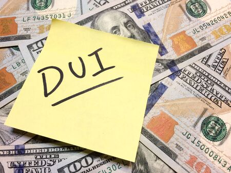 American cash money and yellow post it note with text DUI in black color aerial view