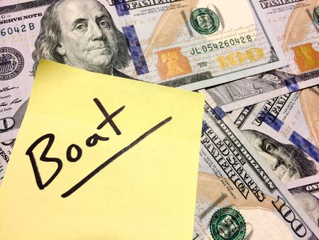 American cash money and yellow post it note with text Boat in black color aerial view