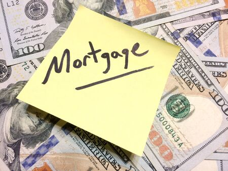 American cash money and yellow post it note with text Mortgage in black color aerial view