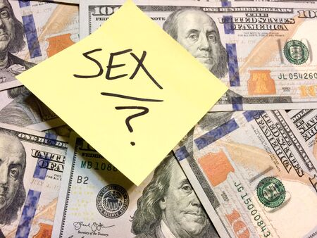 American cash money and yellow post it note with text Sex with question mark in black color aerial view