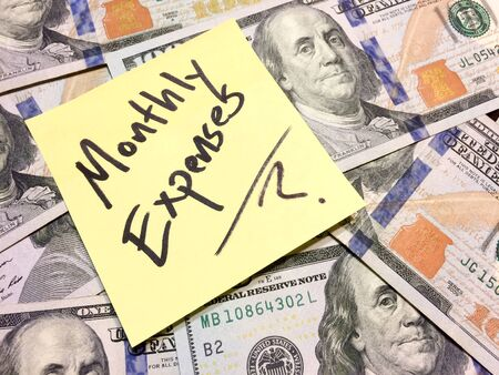 American cash money and yellow post it note with text Monthly Expenses with question mark in black color aerial view