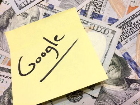 American cash money and yellow paper note with text Google in black color aerial view