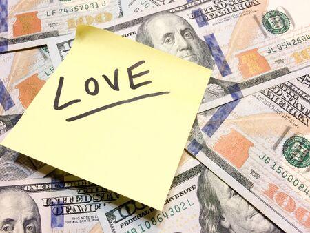 Denaro contante americano e post-it giallo con testo Love in vista aerea di colore nero