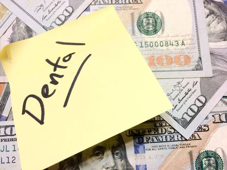 American cash money and yellow post it note with text Dental in black color aerial view Imagens