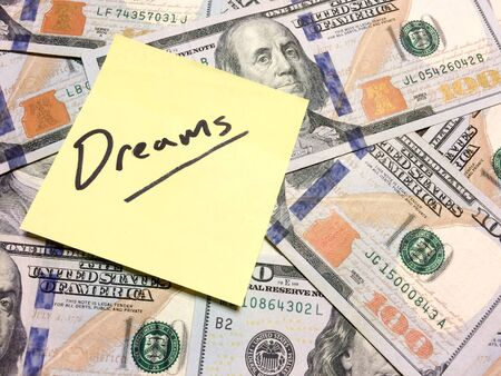 American cash money and yellow post it note with text Dreams in black color aerial view Imagens