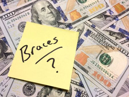 American cash money and yellow post it note with text Braces with question mark in black color aerial view